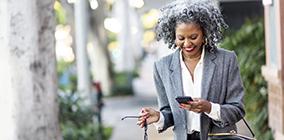 Woman walking on sidewalk smiling while looking at her phone.