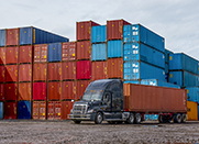 Semi truck hauling container with large stacks of shipping containers behind.