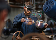 Factory manufacturer wears HoloLens2 headset while manipulating virtual machinery.